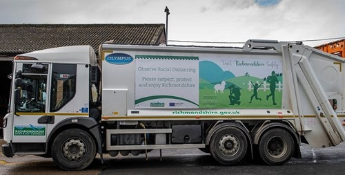 Bin truck with Visit Richmondshire Safely campaign banner